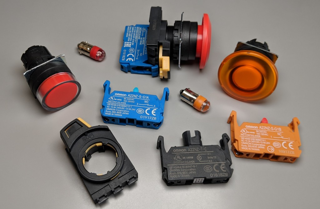 Random Omron switch parts including a shrouded red non-illuminated push button, illuminated mushroom button, a mounting collar, LED, NO contacts, illumination unit, NC contacts, and an assembled non-illuminated mushroom button.