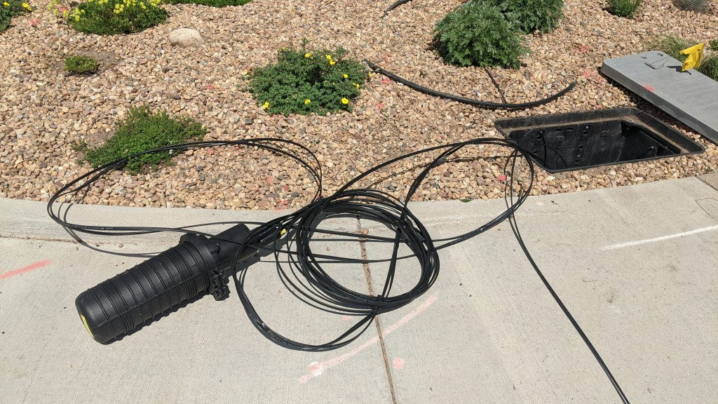 The splice enclosure containing the splices between the 24 fiber count distribution cable and the 2 fiber count drop cable.