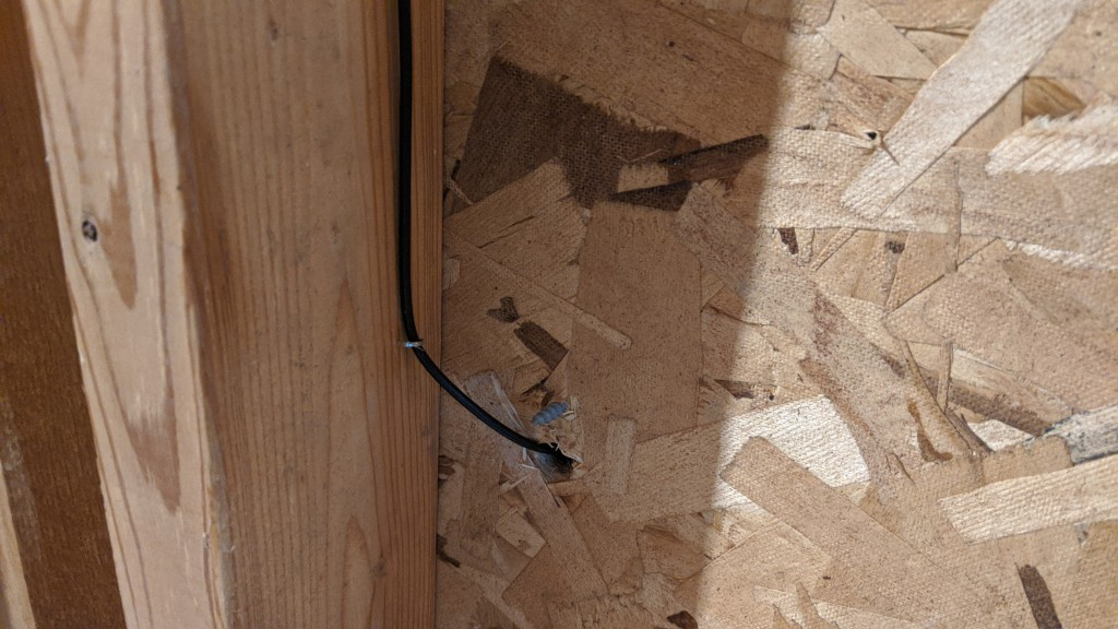 The fiber runs down along a stud to a piece of particle board then into the network closet.
