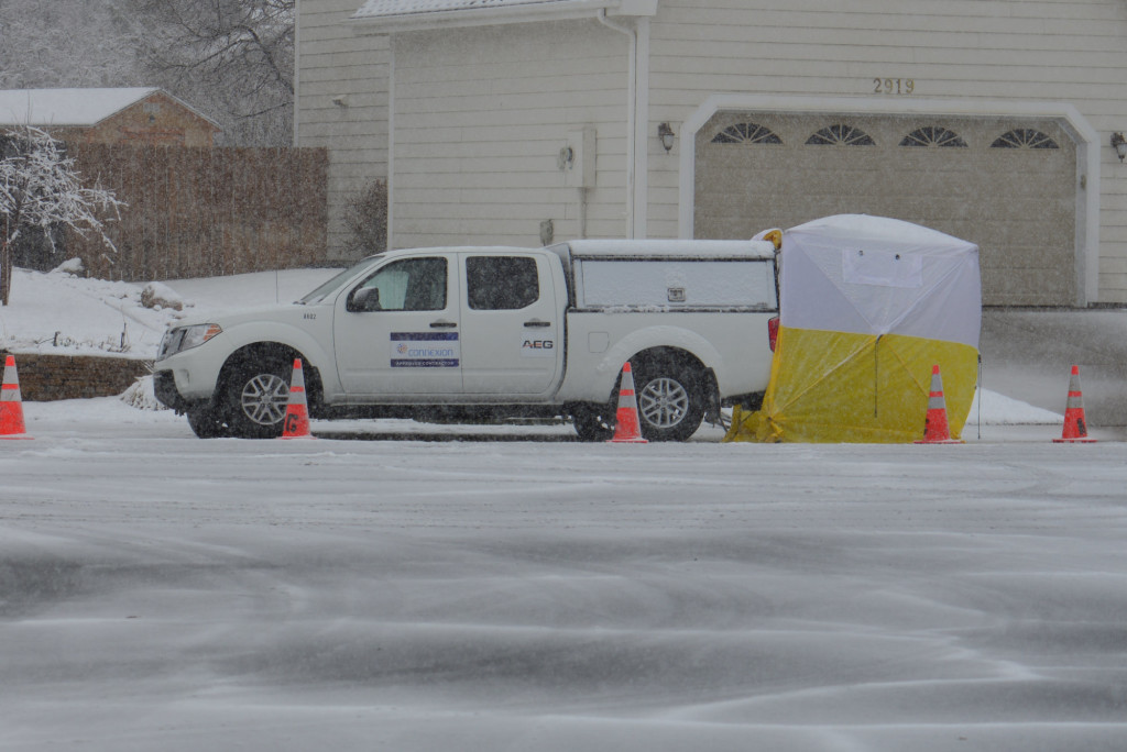 Technicians use a small popup tent while they work on the fiber in the fiber vault across the street.