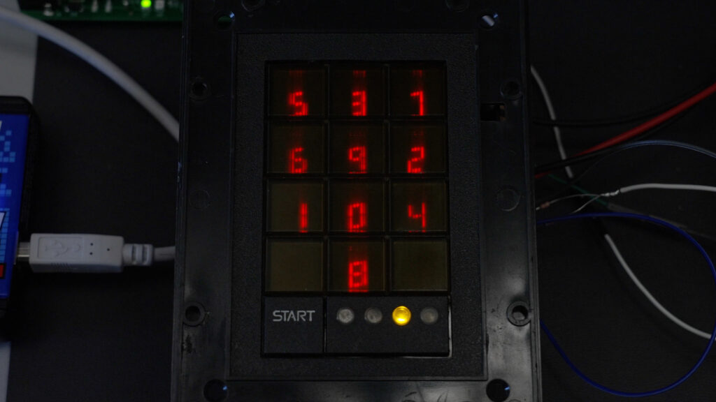 The front face of the Scramblepad with randomized digits shown on the RED LED seven-segment displays.