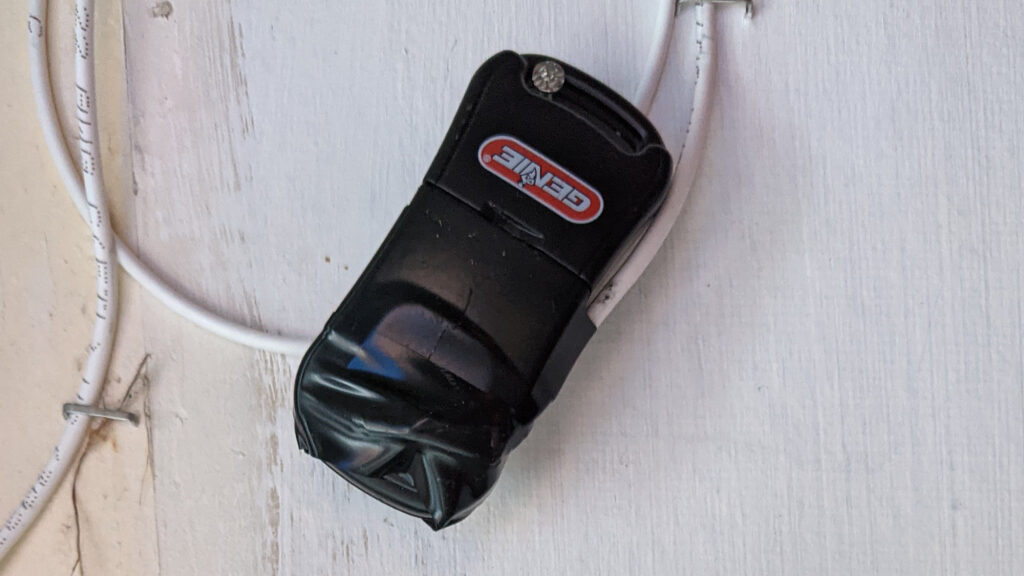 The wireless garage door opener with a set of wires soldered across the pushbutton.